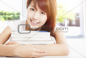 smiling student holding books in the classroom