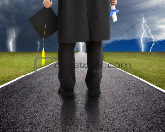 graduate standing on the road and watching the storm