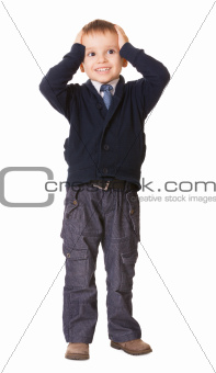 Full-length amazed or surprised child boy holds her head