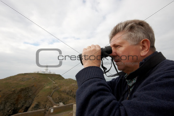Mature man looking through binoculars