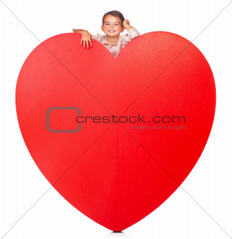 Beautiful little girl with big red heart on white