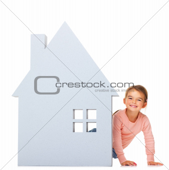 Adorable little child with a big house icon on white