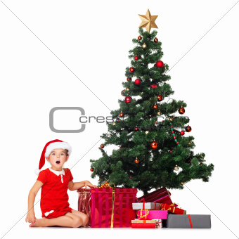 Surprised little girl with Christmas tree and gifts