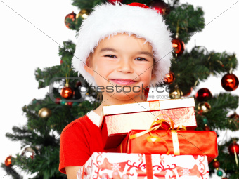 Cute little Santa girl holding gift boxes