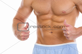 Closeup on man with abdominal muscles showing thumbs up