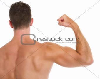 Muscular man showing biceps. Rear view
