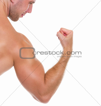 Closeup on muscular man showing biceps