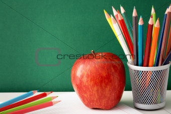 Colorful pencils and apple