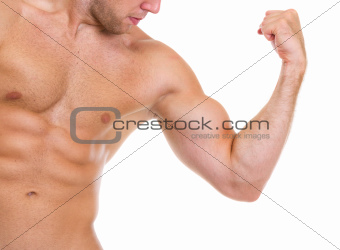 Closeup on muscular man showing abdominal muscles and biceps