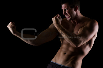 Angry muscular man in attack pose on black