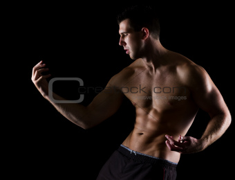 Strong muscular man gracefully posing on black