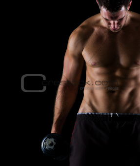 Strong muscular man holding dumbbell on black