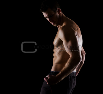 Strong muscular athlete posing on black