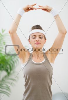 Young woman in sportswear making yoga exercise