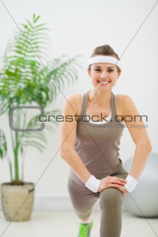 Smiling slim woman making stretching exercises