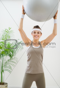Smiling healthy woman making exercise with fitness ball
