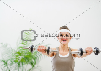 Young sport woman making exercise with dumbbells