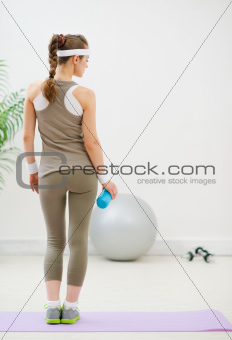 Fitness young woman with battle of water. Rear view