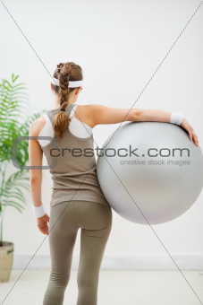 Fitness young woman with fitness ball. Rear view