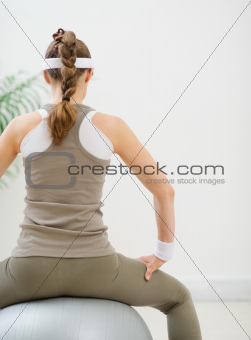 Fitness young woman sitting on fitness ball. Rear view