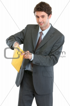 Smiling business man opening letter