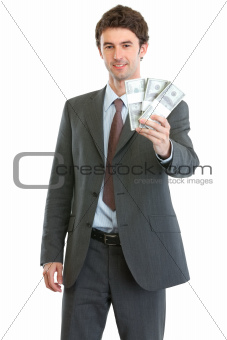 Smiling businessman showing packs of dollars