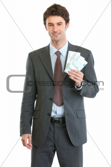 Smiling businessman showing packs of euros