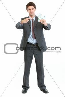 Full length portrait of businessman pointing on packs of euros