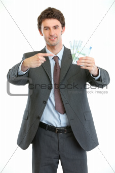 Smiling businessman pointing on packs of euros