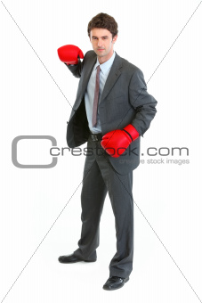 Businessman in boxing gloves swinging arm to strike