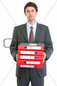 Modern businessman holding pack of folders