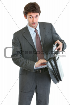 Concerned businessman looking into suitcase