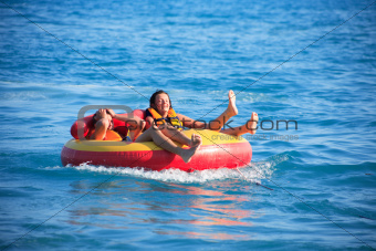 Friends Tubing On Sea