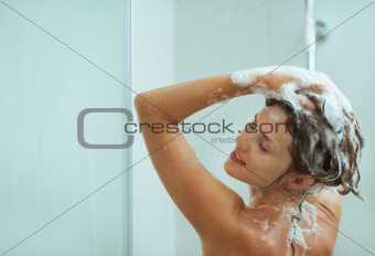 Woman applying shampoo in shower
