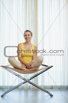 Smiling young woman sitting on modern chair
