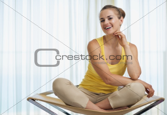 Portrait of smiling young woman sitting on modern chair