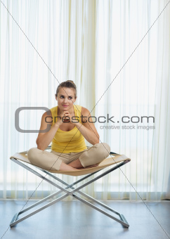 Thoughtful young woman sitting on modern chair
