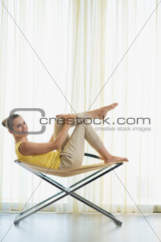 Happy young woman sitting on modern chair