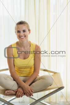 Portrait of happy young woman sitting on modern chair