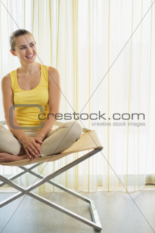 Happy young woman sitting on modern chair and looking on copy space