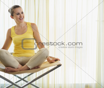 Smiling young woman sitting on modern chair and looking on copy space