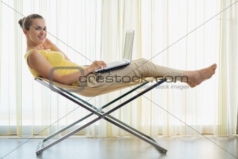 Happy young woman sitting on modern chair and working on laptop