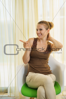 Happy young woman sitting on modern chair and pointing on copy space