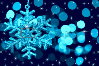 Christmas decoration snowflake  on defocused lights and stars ba