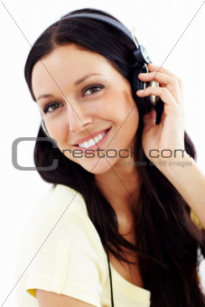 Closeup of a gorgeous brunette wearing headphones and smiling at the camera isolated on a white background