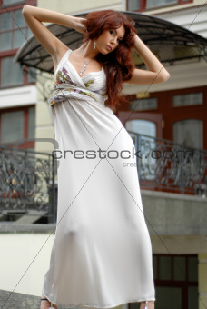 brunette in long dress near old-fashioned hotel
