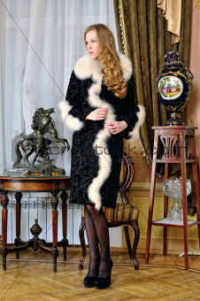 Beautiful woman in fur coat in classical antique interior.