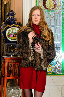 beautiful woman in fur coat. The luxurious antique interior.