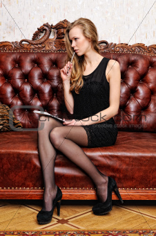 Beautiful woman with book sitting on the sofa in antique interior.