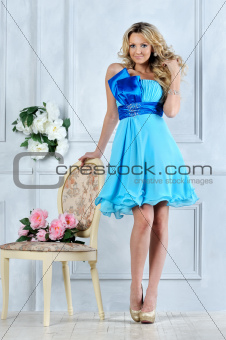 Beautiful blonde woman in blue dress in luxury interior.
